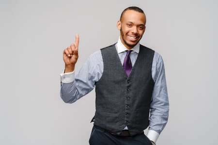 African-American businessmanman showing ONE by finger over grey background