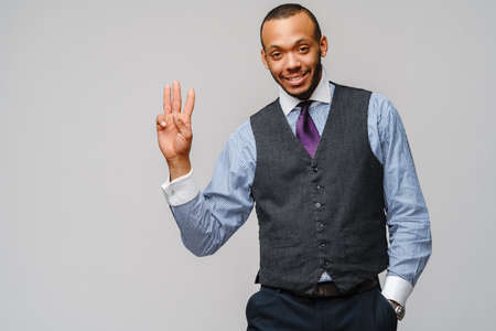 African-American businessmanman showing THREE by finger over grey background