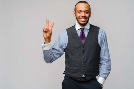 African-American businessmanman showing TWO by finger over grey background