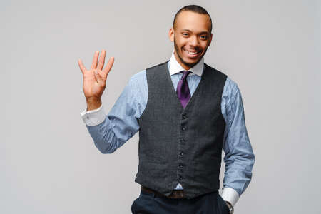 African-American businessmanman showing FOUR by finger over grey background