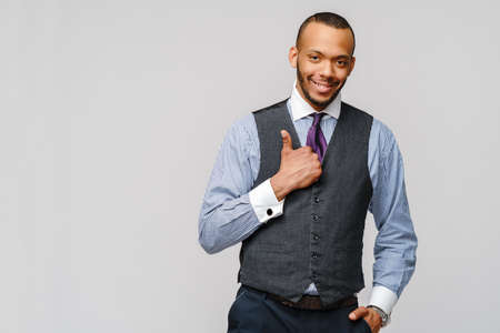 Happy african-american businessman showing his thumb up with smile over grey background Banco de Imagens