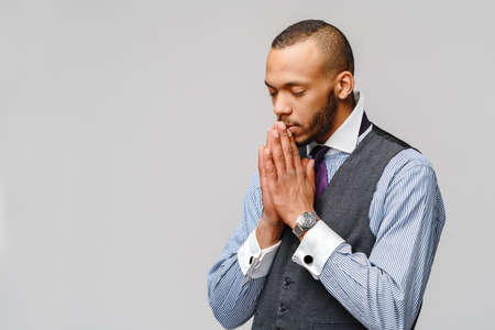 African american man holding hands in prayer hoping for better