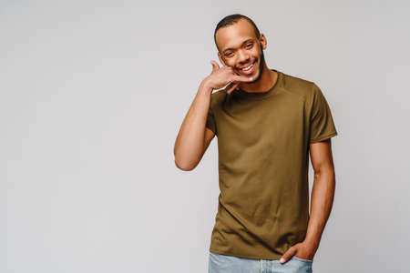 Handsome young African American man showing a call me sign and smiling while standing isolated on grey background