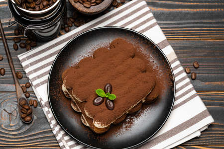Classic tiramisu dessert and coffee grinder on ceramic plate on wooden background