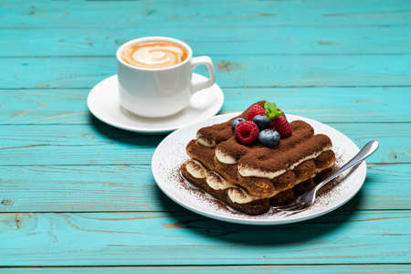portion of Classic tiramisu dessert with raspberries and blueberries and cup of espresso coffee on blue wooden background Archivio Fotografico