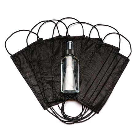 bottle of lotion, sanitizer or liquid soap and medical protective masks over light grey background