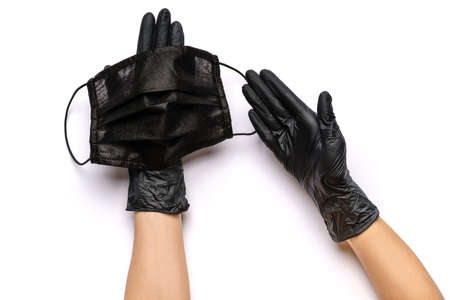 Human hand in protective glove holding face protective masks isolated on white background Standard-Bild