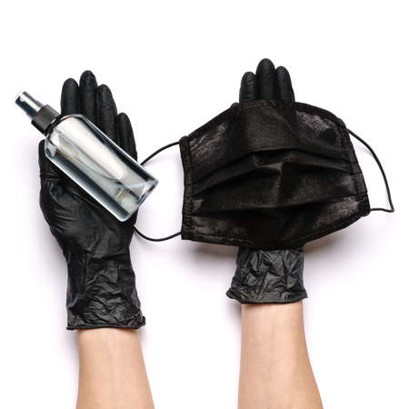 Human hand in protective glove holding face protective masks and alcohol hand sanitizer spray isolated on white background