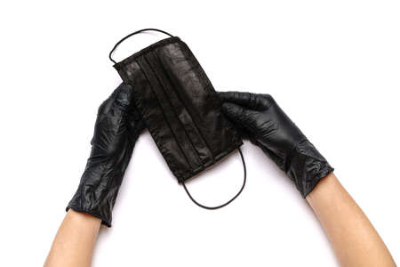 Human hand in protective glove holding face protective masks isolated on white background Standard-Bild - 157341435