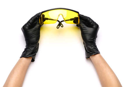 hands with medical latex gloves holding protective goggles on white background Standard-Bild - 157289130