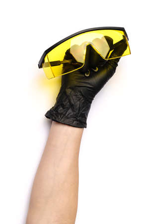 hands with medical latex gloves holding protective goggles on white background