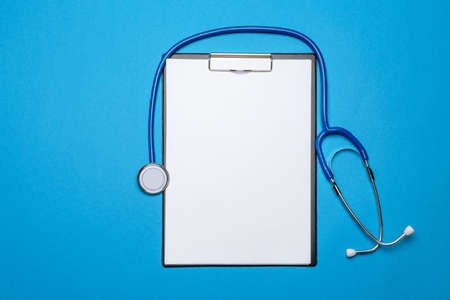 Stethoscope and clipboard with paper over blue background