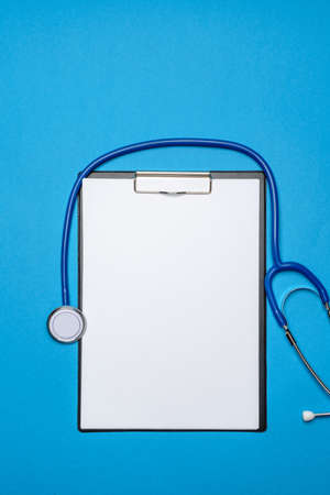 Stethoscope and clipped board with paper over blue background