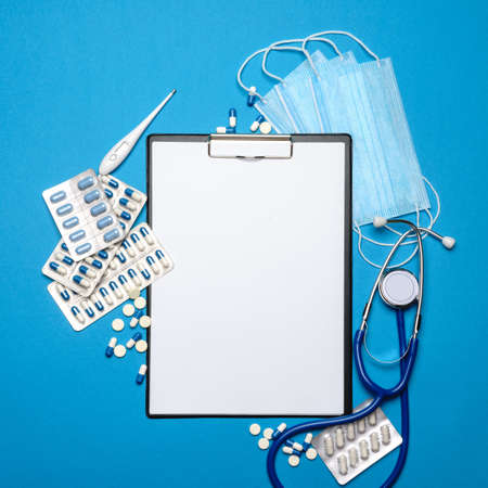 Empty clipboard with medical supplies - pills, protective masks, stethoscope and thermometer