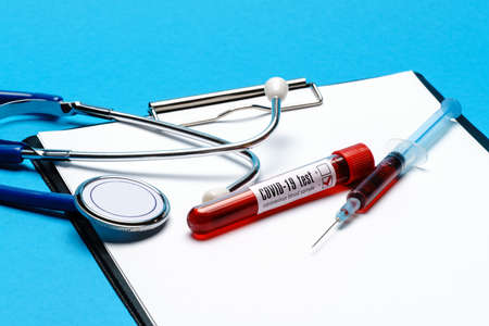 Healthcare concept - Covid-19 negative blood test tube, stethoscope, syringe and clipboard with blank sheet