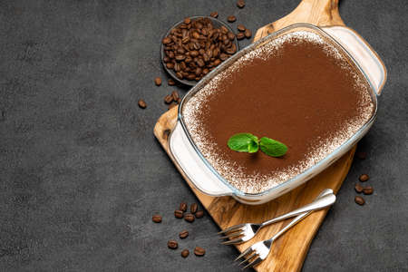 Traditional Italian Tiramisu dessert in glass baking dish on wooden cutting board on concrete background