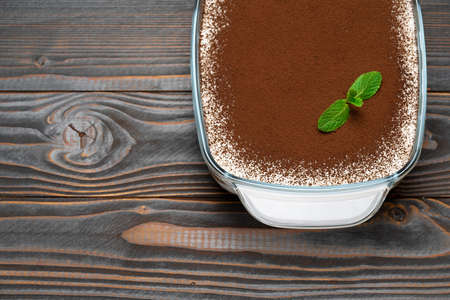 Traditional Italian Tiramisu dessert in glass baking dish on wooden background Standard-Bild