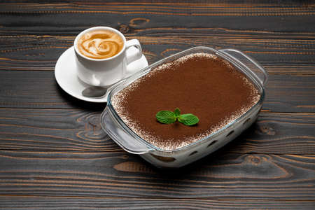 Traditional Italian Tiramisu dessert in glass baking dish and cup of fresh hot espresso coffee on wooden background Standard-Bild