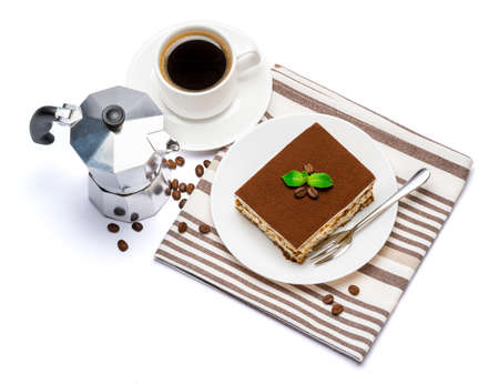 Traditional Italian Tiramisu dessert square portion on ceramic plate, mocha coffee maker and cup of fresh espresso coffee isolated on white background with clipping path