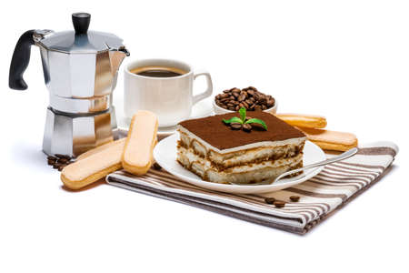 Traditional Italian Tiramisu dessert square portion on ceramic plate, mocha coffee maker, savoiardi cookies and cup of fresh espresso coffee isolated on white background with clipping path Standard-Bild
