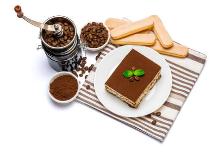 Traditional Italian Tiramisu dessert square portion on ceramic plate, coffee mill grinder and savoiardi cookies a isolated on white background with clipping path Standard-Bild