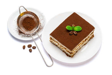 Traditional Italian Tiramisu square dessert portion on ceramic plate and strainer with cocoa powder isolated on white background with clipping path Standard-Bild