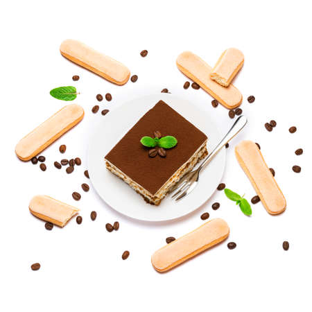 Traditional Italian Tiramisu square dessert portion on ceramic plate, savoiardi cookies and coffee beans isolated on white Standard-Bild