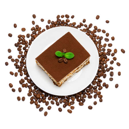 Traditional Italian Tiramisu square dessert portion on ceramic plate and coffee beans isolated on white Standard-Bild