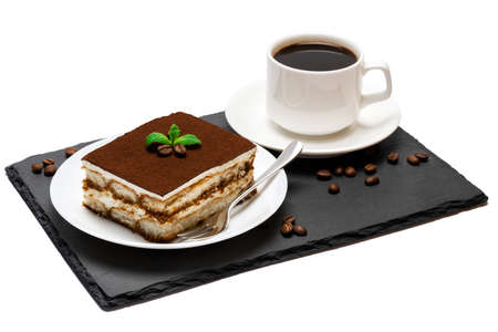 Traditional Italian Tiramisu dessert square portion on ceramic plate and cup of fresh espresso coffee on stone serving cutting board isolated on white