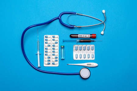 Stethoscope, syringe, test tubes with blood samles and ampoules with medicine or vaccine over blue background