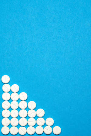 group of round white pills on blue background