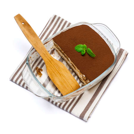 Traditional Italian Tiramisu dessert in glass baking dish isolated on white background