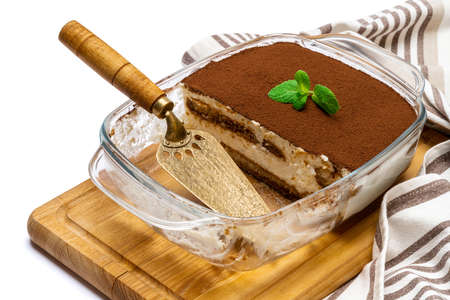 Traditional Italian Tiramisu dessert in glass baking dish on wooden cutting board isolated on white background