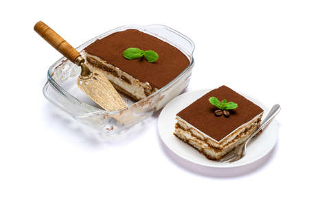 Traditional Italian Tiramisu dessert in glass baking dish, portion on plate and scapula isolated on white background
