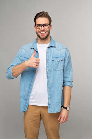 Portrait of young handsome caucasian man in jeans shirt showing big thumb up gesture standing over light background 스톡 콘텐츠