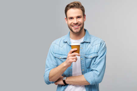 Portrait of young handsome caucasian man in jeans shirt over light background holding cup of coffee
