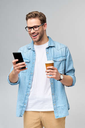 pretty casual man in blue jeans shirt holding his phone and cup of coffee to go standing over studio grey background