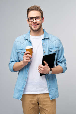 Happy young man wearing jeans shirt standing and using tablet pc pad and holding cup of coffee to go standing over studio grey background