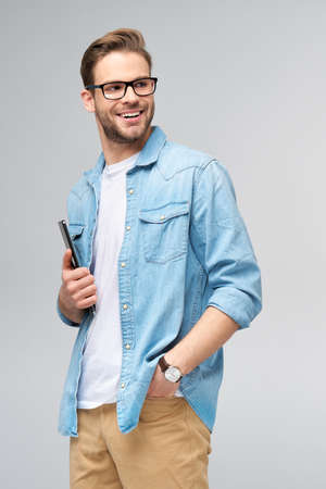 Happy young man wearing jeans shirt standing and using tablet over studio grey background