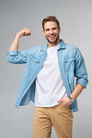 Portrait of a handsome man in jeans shirt showing his bicep with arm bended over grey background Imagens