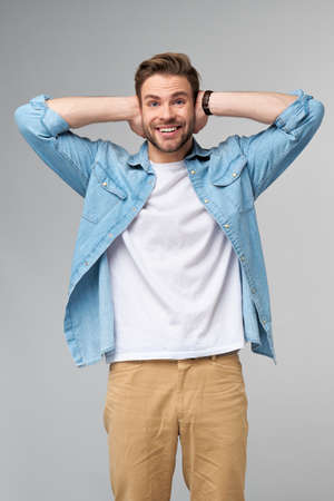 young man with ears closed standing over grey studio background 免版税图像