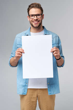 Portrait of a happy handsome young man holding blank white card or sign over white background
