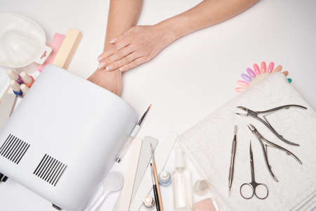 manicure and pedicure items - nail polish drying lamp, nail file, scissors and brushes over light background