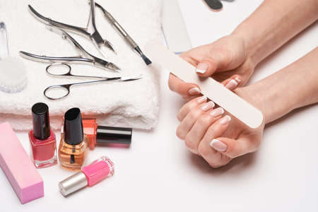 top view of manicure tools set for nail care over light background - brush, scissors, nail polish, file and tweezers Imagens