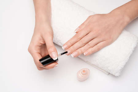 Woman making manicure by herself on grey background
