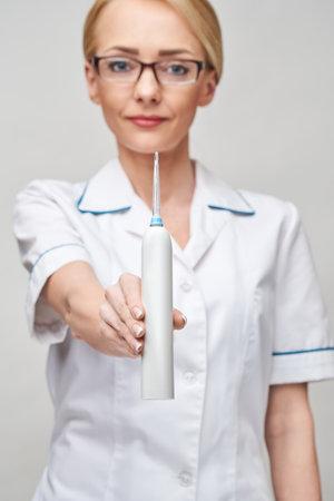 female dentist doctor shows irrigator hygiene equipment for careful teeth cleaning