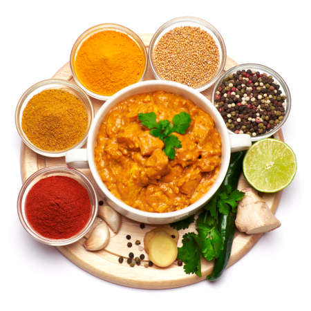 Plate of Traditional Chicken Curry and set of spices on white background