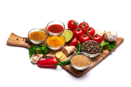 Set of spices and vegetables on wooden serving board on white background Stockfoto