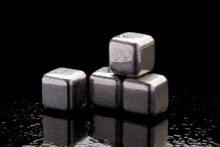 Steel cooling cubes for cocktail drink on glass background Stockfoto