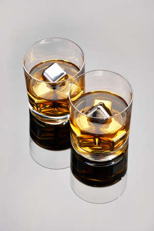 Whiskey with steel cooling cubes on dark glass background